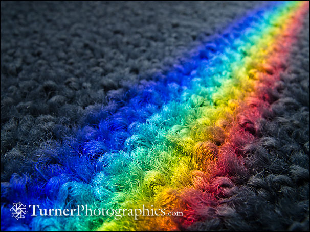 Rainbow on carpet from prism effect of glass shelf