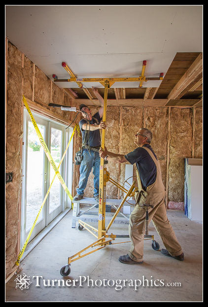 Adam and Mike raise and place ceiling drywall in camera room