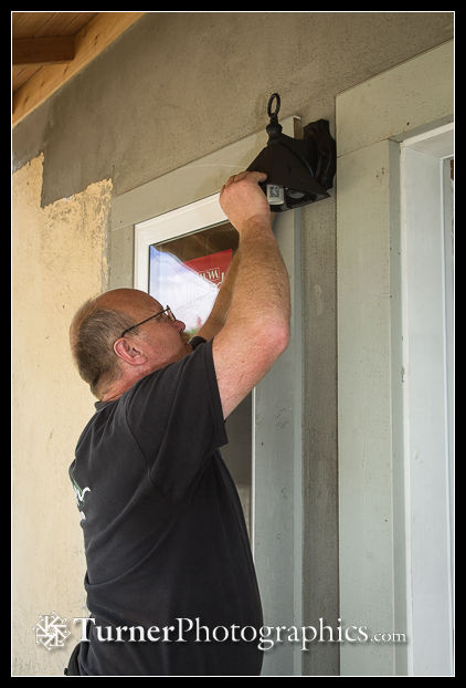 Electrician installs front door outside light.