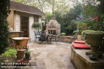 0717518 Flagstone patio w/ stone fireplace, outdoor dining set, red cushions on curving low stone wall, garden shed [Taxus sp.; Hibiscus cv.]. Stenseth, Oklahoma City, OK. © Mark Turner