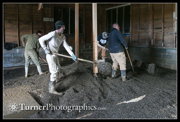 Crew spreads and levels the gravel by hand.