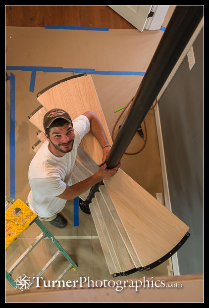 Matt holds spiral staircase pole in position