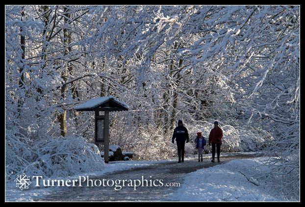 Family walks snowy Railroad Trail